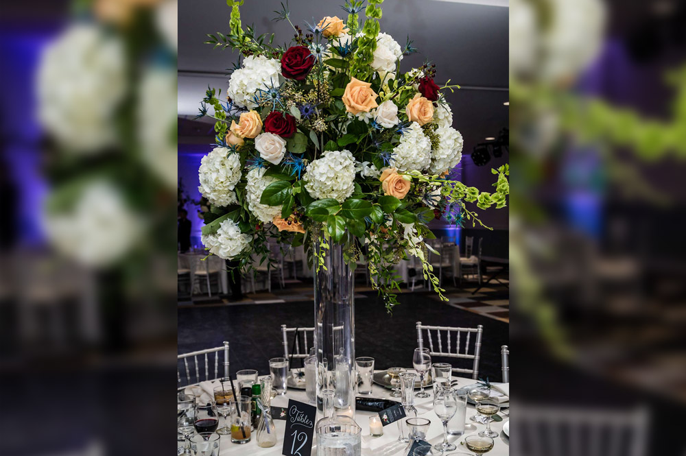 Reception in ballroom, flowers in tall vase, tables decorated for reception